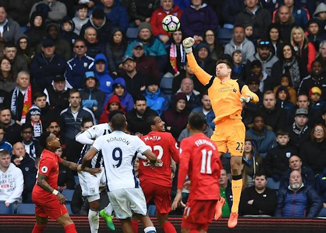 Liverpool's goalkeeper Simon Mignolet (R) punches the ball clear during the English Premier League football match between West Bromwich Albion and Liverpool at The Hawthorns stadium in West Bromwich, central England, on April 16, 2017 (AFP Photo/Justin TALLIS)