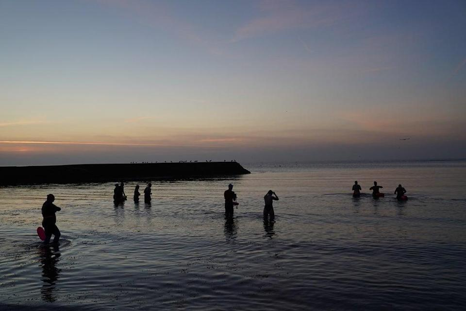 Sea swimmers head out before sunrise at Cullercoats Bay on the north-east coast (Owen Humphreys/PA) (PA Wire)