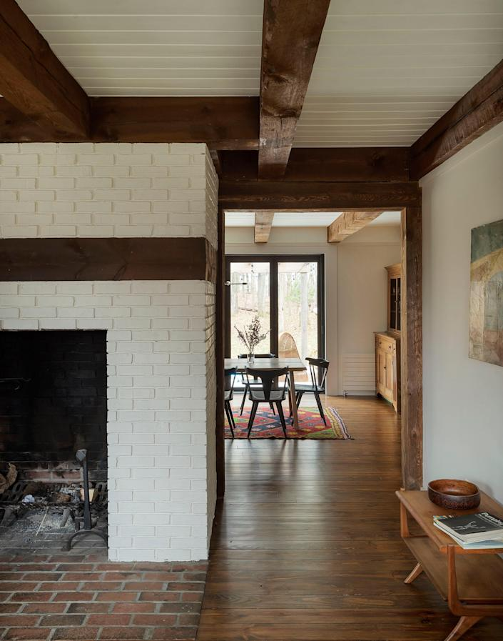 AFTER: The largest of several fireplaces in the house, this brick fireplace was painted in Farrow & Ball's Slipper Satin, to match the surrounding walls. The heavy timber beams were left exposed and unfinished throughout.