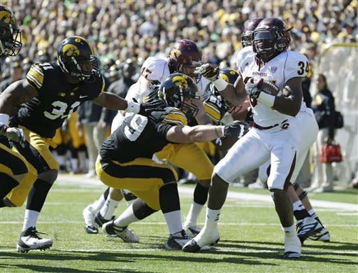 Central Michigan running back Zurlon Tipton, right, breaks free from Iowa linebacker Anthony Hitchens, left, defensive lineman Dominic Alvis, center, during a first quarter touchdown run in an NCAA college football game, Saturday, Sept. 22, 2012, in Iowa City, Iowa. (AP Photo/Charlie Neibergall)