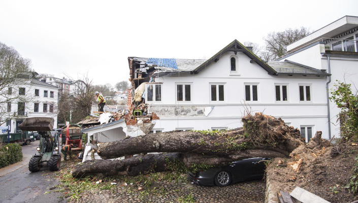 A tree lies on a car in Hamburg, Germany, Monday, Feb. 10, 2020. A storm battered the U.K. and northern Europe with hurricane-force winds and heavy rains Sunday, halting flights and trains and producing heaving seas that closed down ports. Soccer games, farmers' markets and cultural events were canceled as authorities urged millions of people to stay indoors, away from falling tree branches. (Daniel Bockwoldt/dpa via AP)