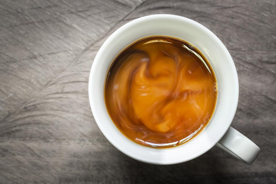Cup of coffee with flowing milk on wooden background