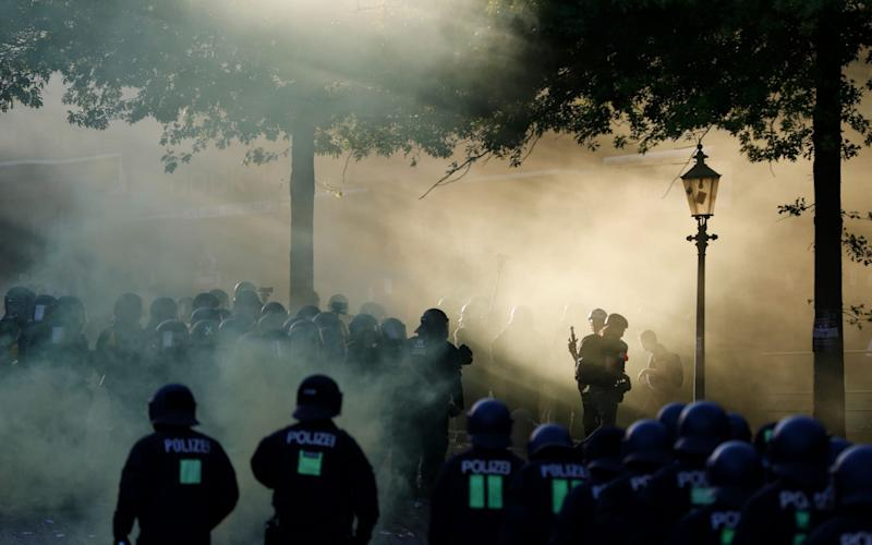 "Riot police move in through the smoke during the ""Welcome to Hell"" rally against the G20 summit in Hamburg, - Credit: AFP"