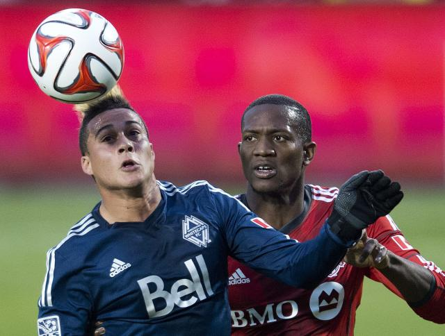 Toronto FC defender Doneil Henry, right, battles for the ball against Vancouver Whitecaps forward Erik Hurtado, left, during first half semi-final Amway Canadian Championship soccer action in Toronto on Wednesday, May 7, 2014. (AP Photo/The Canadian Press, Nathan Denette)