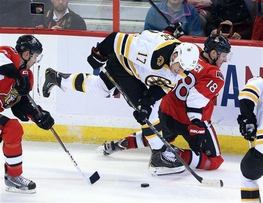 Boston Bruin Milan Lucic (17) attempts to get possession of the puck from Ottawa Senator Chris Phillips (4) during second period NHL hockey action in Ottawa Monday March 11, 2013. (AP Photo/The Canadian Press, Fred Chartrand)