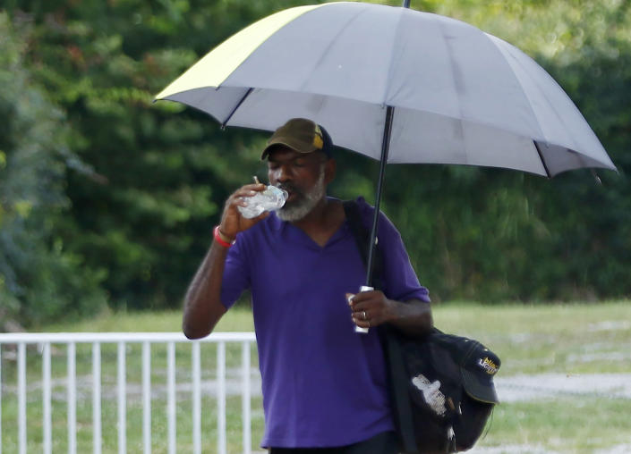 """For Gregory Jones of Jackson, Miss., any walk in this """"heat and sun means using my umbrella for shade,"""" he said Tuesday, Aug. 13, 2019, as he hydratred while walking home in the Farish Street historical district. """"My umbrella is not just for the rain."""" Weather forecasters warned of heat advisories climbing past 100 degrees in much of the South, from Texas to parts of South Carolina. (AP Photo/Rogelio V. Solis)"""