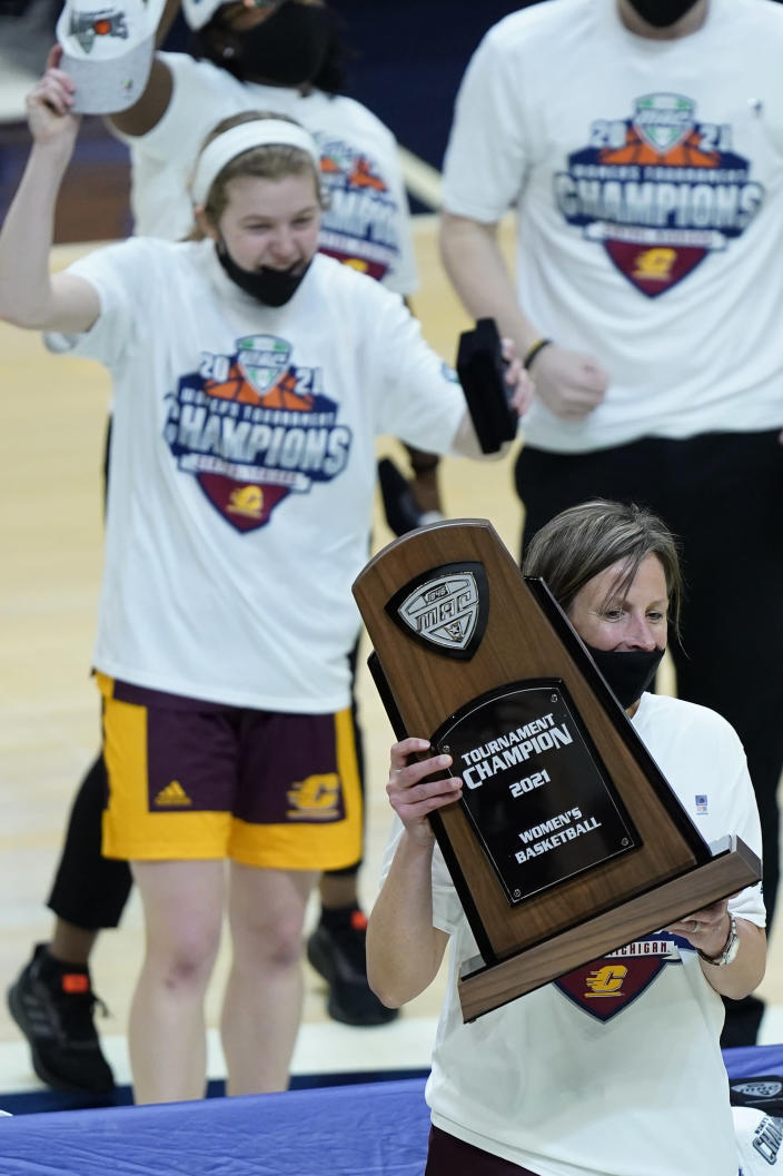 Central Michigan's head coach Heather Oesterle holds up the trophy after Central Michigan defeated Bowling Green 77-72 in an NCAA college basketball game in the championship of the Mid-American Conference tournament, Saturday, March 13, 2021, in Cleveland. (AP Photo/Tony Dejak)