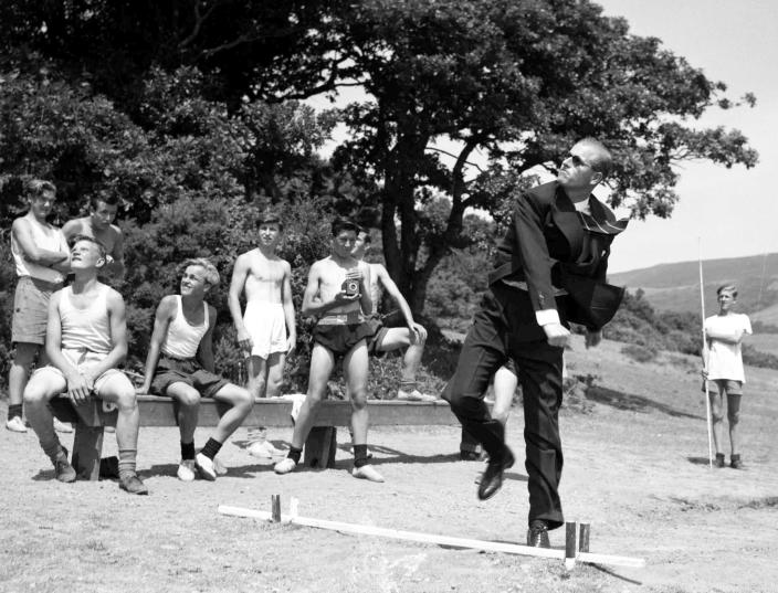 FILE - In this July 12, 1949 file photo, the Duke of Edinburgh throws a javelin during a visit to the Outward Bound Sea School, in Wales, watched by some of the boys. Buckingham Palace officials say Prince Philip, the husband of Queen Elizabeth II, has died, it was announced on Friday, April 9, 2021. He was 99. Philip spent a month in hospital earlier this year before being released on March 16 to return to Windsor Castle. Philip, also known as the Duke of Edinburgh, married Elizabeth in 1947 and was the longest-serving consort in British history. (AP Photo/Leslie Priest, File)
