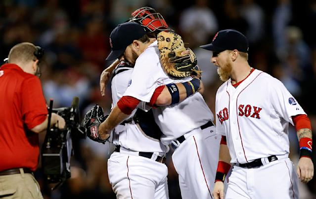 Boston Red Sox's John Lackey, center right, hugs Jarrod Saltalamacchia, center left, after pitching a complete game and defeating the Baltimore Orioles 3-1 in a baseball game in Boston, Thursday, Sept. 19, 2013. Boston Red Sox's Mike Carp looks on at right. (AP Photo/Michael Dwyer)