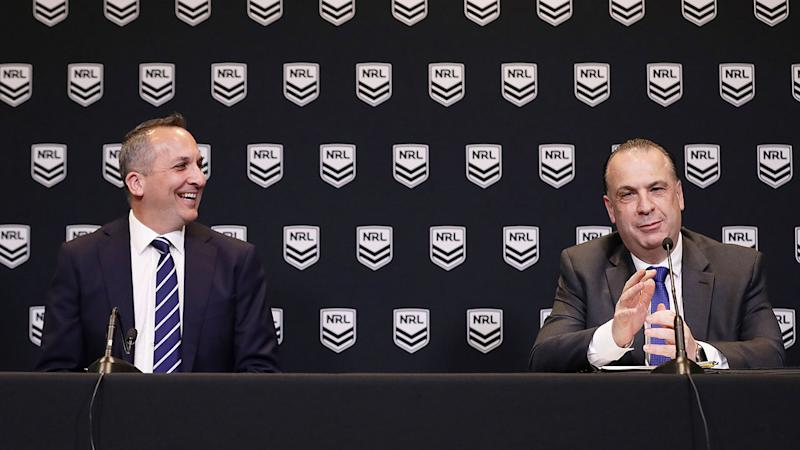 On the right, Peter V'landys speaks at a press conference while Andrew Abdo laughs on the left.
