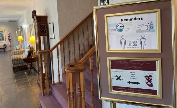 A sign reminds people attending funerals to mask up, sanitize and keep their distance which means no handshakes or hugs.  (Jodi Swan - image credit)