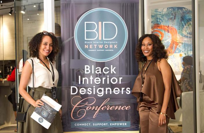 Black Interior Designers Network President Keia McSwain stands in front of a BIDN conference banner.