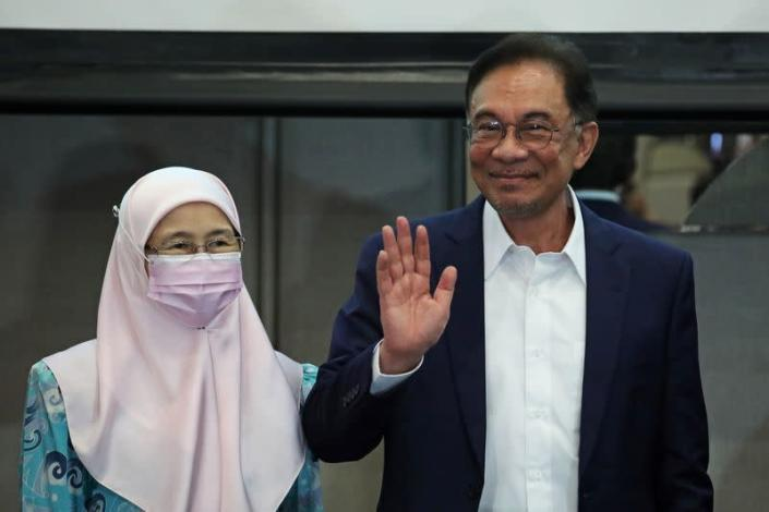 Malaysia opposition leader Anwar Ibrahim and his wife Wan Azizah Wan Ismail react after a news conference in Kuala Lumpur