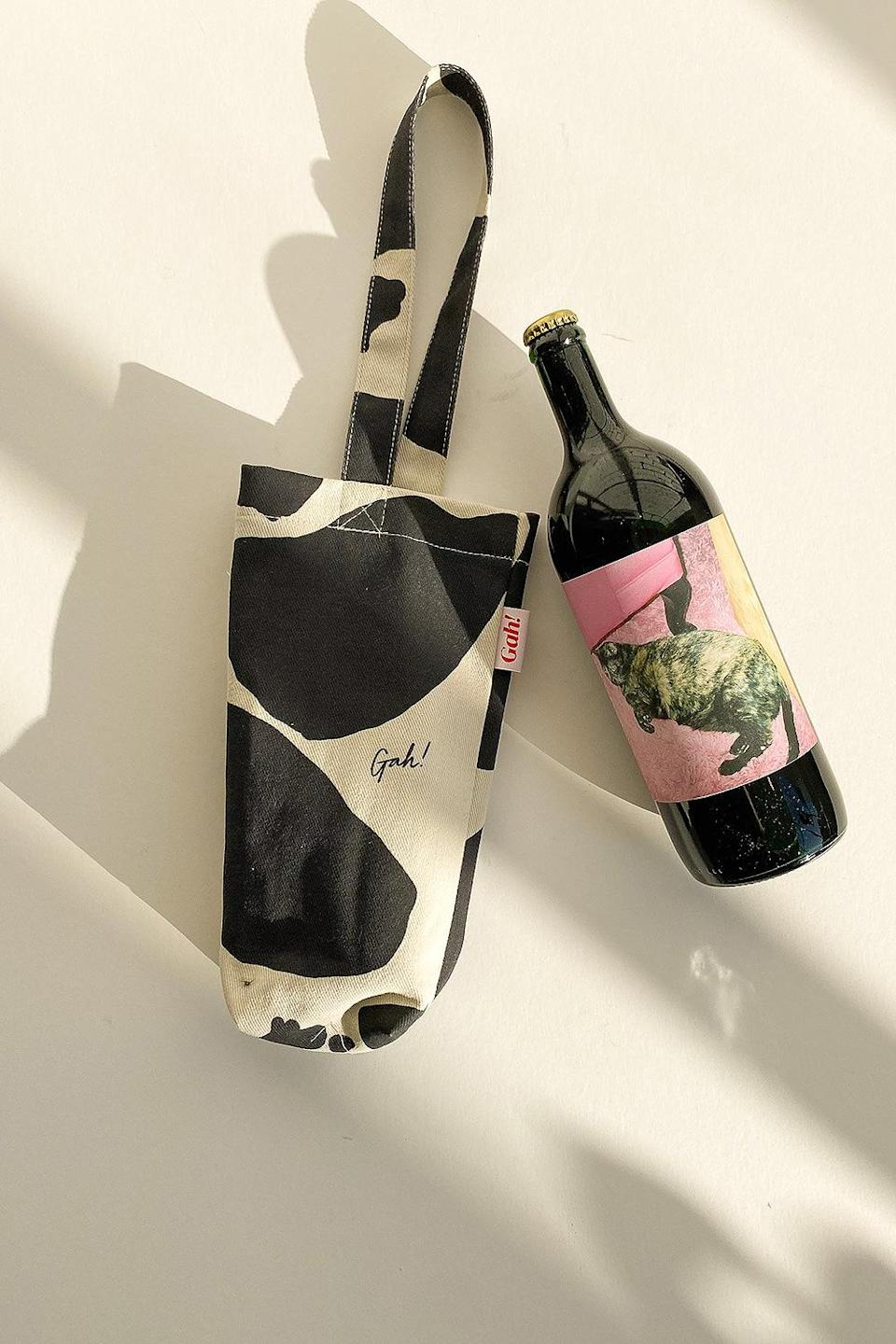 """<p><em>Moo-ve</em> over plastic bags — this reusable tote pairs perfectly with a bottle of wine, whether you're gifting it or enjoying it at home. It comes in a variety of patterns, but the of-the-moment cow print is easy to incorporate into any outfit. The denim tote is perfectly sized to carry a bottle of wine, but you can use it for any beverage of your choice. </p> <p><strong>Buy It!</strong> $25, <a href=""""https://lsg.zlwlj8.net/c/249354/42530/10895?subId1=PEOGeniusHolidayGiftIdeasUnder25sdodd1271LifGal12372801202011I&u=https%3A%2F%2Flisasaysgah.com%2Fcollections%2Flisa-says-gah%2Fproducts%2Fdenim-wine-tote-black-ivory-cow"""" rel=""""nofollow noopener"""" target=""""_blank"""" data-ylk=""""slk:lisasaysgah.com"""" class=""""link rapid-noclick-resp"""">lisasaysgah.com</a></p>"""