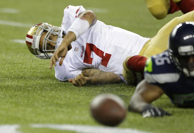 San Francisco 49ers quarterback Colin Kaepernick (7) watches his fumbled ball bounce away as Seattle Seahawks' Cliff Avril eyes it as well in the first half of an NFL football game, Sunday, Sept. 15, 2013, in Seattle. The Seahawks recovered the ball on the play. (AP Photo/Elaine Thompson)