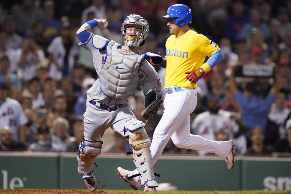 New York Mets catcher Tomas Nido, left, forces out Boston Red Sox's Jose Iglesias, right, as he turns a bases-loaded double play on a ground out by Xander Bogaerts in the third inning of a baseball game at Fenway Park, Tuesday, Sept. 21, 2021, in Boston. (AP Photo/Charles Krupa)