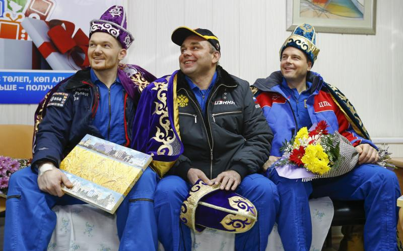 REFILE - CLARIFYING DATE OF LANDING IN SECOND SENTENCE International Space Station (ISS) crew members Alexander Gerst of Germany (L), Maxim Suraev of Russia (C) and Reid Wiseman of the U.S. are presented with the Kazakh national costume during a news conference in Kostanay, northern Kazakhstan November 10,  2014. A veteran Russian cosmonaut and two International Space Station crewmates, one from the United States and one from Germany, returned safely to Earth on Monday with a parachute landing of their Soyuz capsule in Kazakhstan, ending 5-1/2 months in orbit. REUTERS/Shamil Zhumatov (KAZAKHSTAN - Tags: SCIENCE TECHNOLOGY SOCIETY)