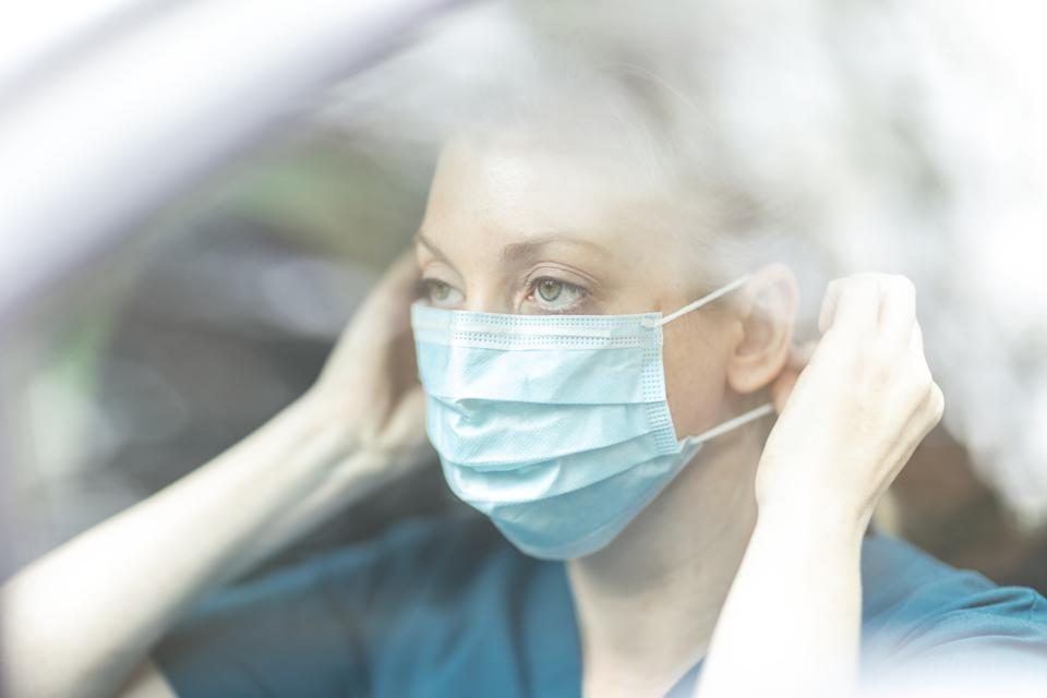 Female community nurse putting on protective mask in car.