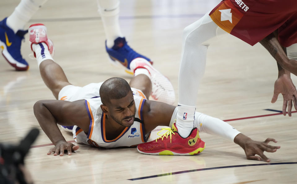 Phoenix Suns guard Chris Paul falls on the floor while pursuing a loose ball in the first half of Game 4 of an NBA second-round playoff series agtainst the Denver Nuggets Sunday, June 13, 2021, in Denver. (AP Photo/David Zalubowski)