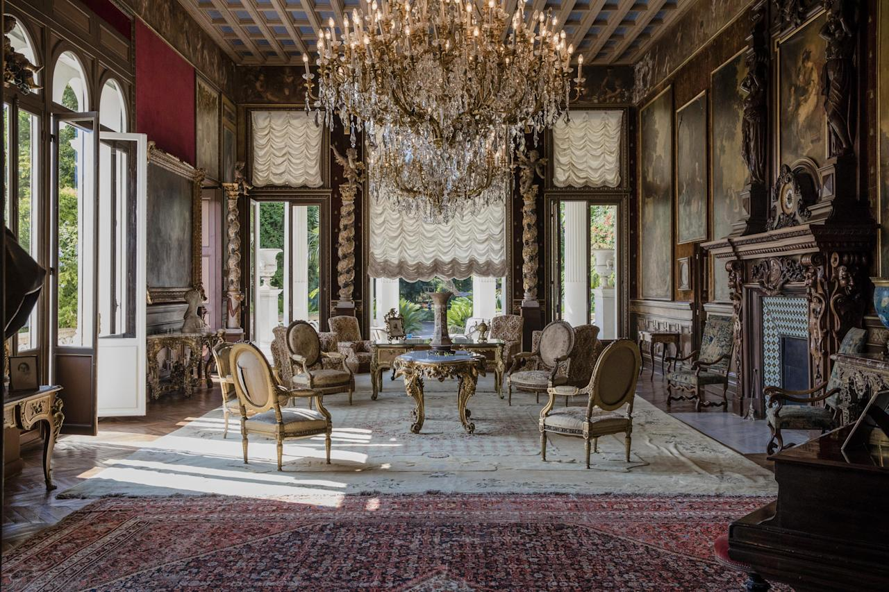 <p>Armchairs and tables stand beneath chandeliers as 19th century portraits in ornate frames adorn the walls of a sitting room inside the villa. </p>