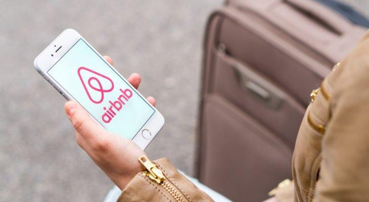 ABNB stock Woman holding mobile phone with the Airbnb logo on the screen