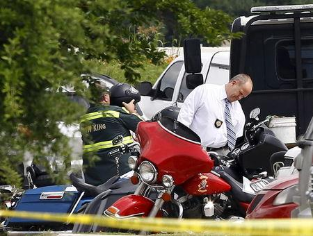 A police officer inspects a motorcycle before it is towed away from the Twin Peaks restaurant, where nine members of a motorcycle gang were shot and killed, in Waco, May 19, 2015. REUTERS/Mike Stone