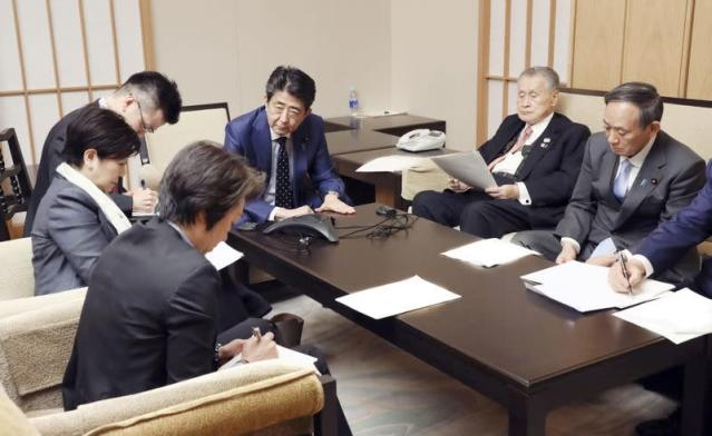 FILE PHOTO: Japan's PM Abe attends a telephone conference with IOC President Bach in Tokyo