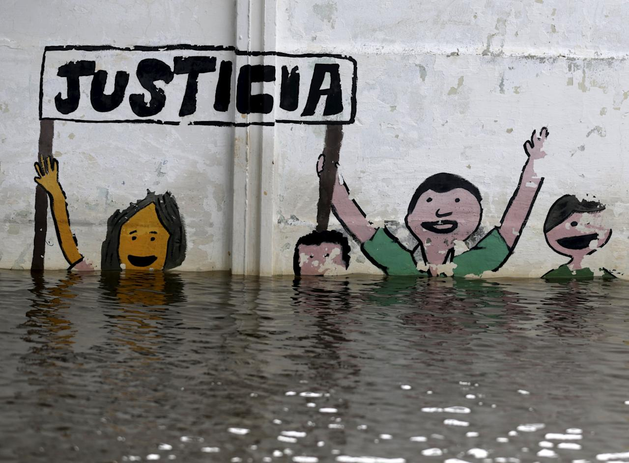 "Graffiti saying ""justice"" partially seen above flood waters in Asuncion, December 27, 2015. More than 100,000 people have had to evacuate from their homes in the bordering areas of Paraguay, Uruguay, Brazil and Argentina due to severe flooding in the wake of heavy summer rains brought on by El Niño, authorities said on Saturday. REUTERS/Jorge Adorno"