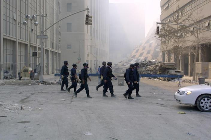 <p>New York Police Department members on patrol in the World Trade Center complex in New York, Sept. 13, 2001. At center is the collapsed 7 World Trade Center. (Photo: James Estrin/AFP/Getty Images) </p>