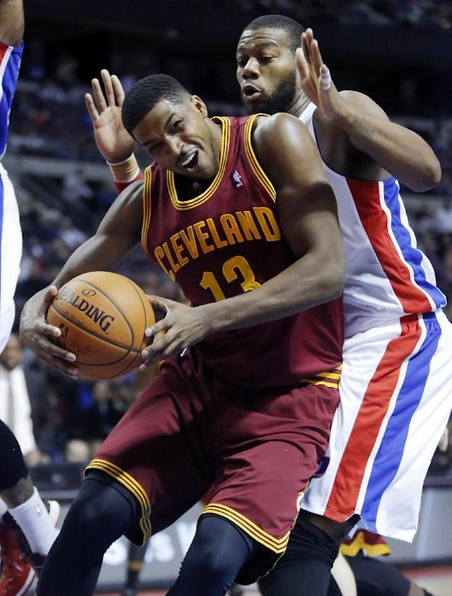 Cleveland Cavaliers forward Tristan Thompson (13) pushes back against Detroit Pistons center Greg Monroe to get a shot during the first half of an NBA basketball game Wednesday, Feb. 12, 2014, in Auburn Hills, Mich. (AP Photo/Duane Burleson)