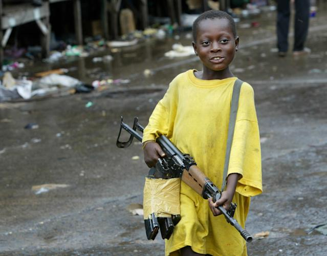 <p>A small boy brandishes an assault rifle near the front lines August 3, 2003 in Monrovia, Liberia. Very small children often hang around the fronts, learning to carry weapons in preparation as roles as fighters. Fighting has been dragging on for nearly two weeks now, leaving downtown's social services nearly non-existent. (Photo by Chris Hondros/Getty Images) </p>