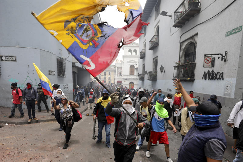 A protester waves a desecrated national flag in a march against President Lenin Moreno and his economic policies during a nationwide strike, in Quito, Ecuador, Wednesday, Oct. 9, 2019. Ecuador's military has warned people who plan to participate in a national strike over fuel price hikes to avoid acts of violence. The military says it will enforce the law during the planned strike Wednesday, following days of unrest that led Moreno to move government operations from Quito to the port of Guayaquil. (AP Photo/Carlos Noriega)