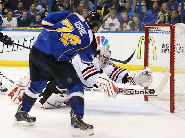 Chicago Blackhawks goaltender Corey Crawford dives back across the crease to try and stop a wide-open shot by St. Louis Blues right wing T.J. Oshie in third period action during Game 5 of a Western Conference quarterfinal playoff game Friday, April 25, 2014, at the Scottrade Center in St. Louis. (AP Photo/The St. Louis Post-Dispatch, Chris Lee)
