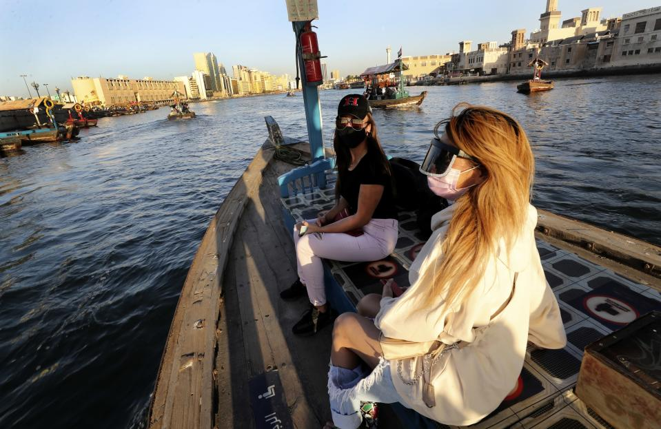 April Joy, vocalist, rear, and Catherine Gallano, dancer and lead choreographer cross the creek water on a boat in Dubai, United Arab Emirates, Wednesday, Oct. 28, 2020. As the coronavirus pandemic mutes Dubai's live-music scene, the Filipino show bands that long have animated the city's storied nightlife are being disproportionately squeezed. Many are out of work and out of money, struggling to survive in overcrowded dormitories at the mercy of employers (AP Photo/Kamran Jebreili)