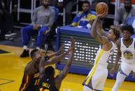 Golden State Warriors guard Kelly Oubre Jr. (12) shoots over Atlanta Hawks forward Tony Snell (19) and center Clint Capela (15) during the first half of an NBA basketball game in San Francisco, Friday, March 26, 2021. (AP Photo/Tony Avelar)