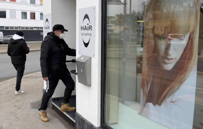 A man in a mask goes to a reopened hairdresser after lock down in Vienna, Austria, Monday, Feb. 8, 2021. The Austrian government has moved to restrict freedom of movement for people, in an effort to slow the onset of the COVID-19 coronavirus. (AP Photo/Ronald Zak)