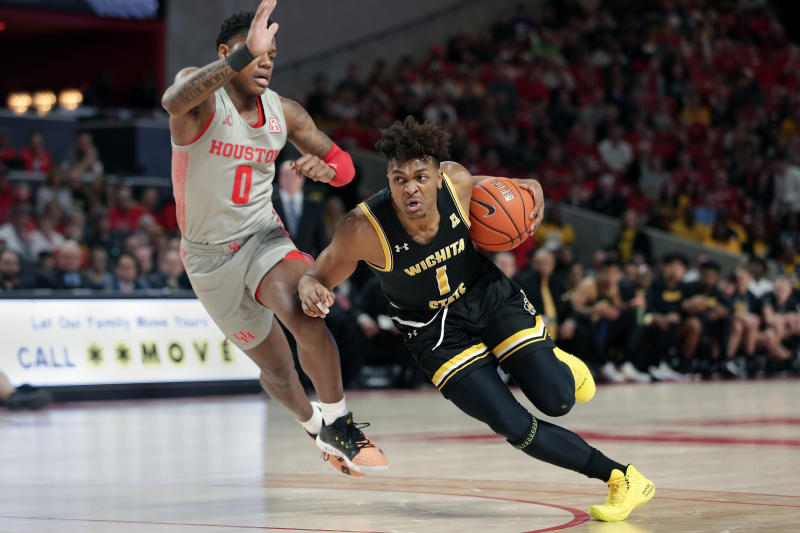 Wichita State guard Tyson Etienne (1) drives around Houston guard Marcus Sasser (0) during the first half of an NCAA college basketball game Sunday, Feb. 9, 2020, in Houston. (AP Photo/Michael Wyke)