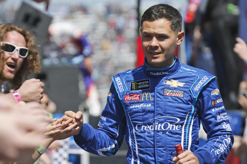FILE - In this March 24, 2019, file photo, NASCAR Cup Series driver Kyle Larson (42) greets fans during driver introductions prior to the NASCAR Cup Series auto race at the Martinsville Speedway in Martinsville, Va. Larson will be back in NASCAR next season driving the flagship No. 5 Chevrolet for Hendrick Motorsports. Larson signed a multi-year contract Wednesday morning with Hendrick that ended his seven-month banishment from NASCAR for using a racial slur while playing an online racing game.(AP Photo/Steve Helber, File)