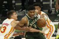 Milwaukee Bucks' Giannis Antetokounmpo tries to get past Atlanta Hawks' Bogdan Bogdanovic (13) and John Collins during the first half of Game 1 of the NBA Eastern Conference basketball finals game Wednesday, June 23, 2021, in Milwaukee. (AP Photo/Morry Gash)