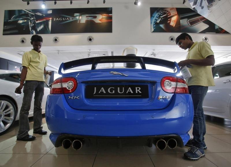 Showroom attendants polish a Jaguar vehicle at a Jaguar Land Rover showroom in Mumbai