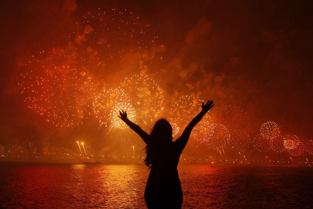 A woman celebrates the New Year as she watches fireworks exploding above Copacabana beach in Rio de Janeiro January 1, 2013. More than two million people gathered along Rio's most famous beach to witness the 20-minute display and celebrate the beginning of a new year.