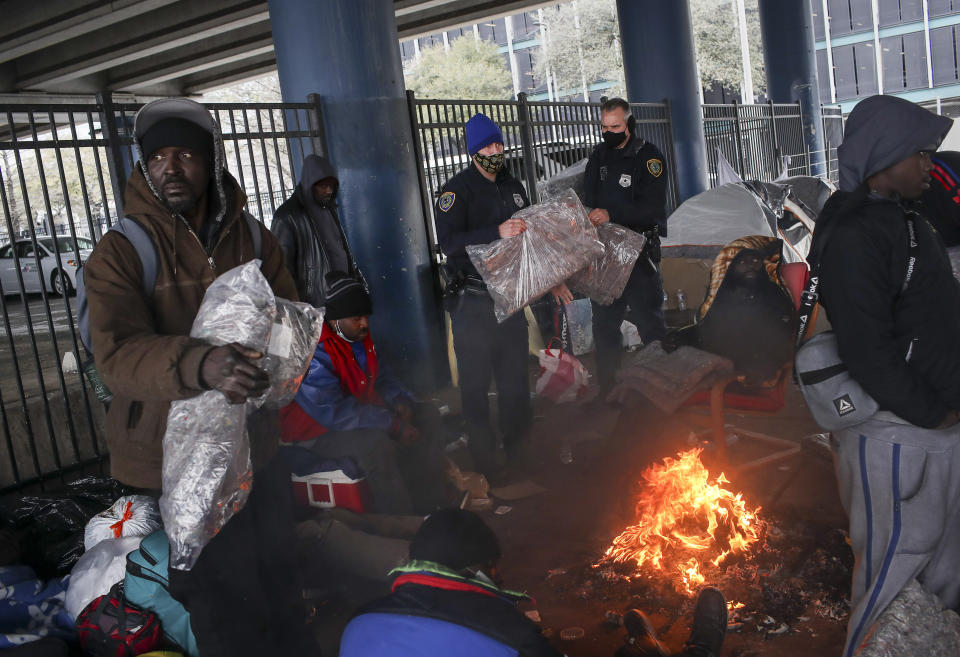 FILE - In this Feb. 16, 2021, file photo, Houston Police officers Kenneth Bigger, center, and Aaron Day, center right, hand out blankets to people under the elevated portion of I-45 in Houston as a winter weather continues to hit the area. Making decisions about risks — large or small — in the pandemic era is fraught enough. But the storms and outages ravaging Texas and other states have added a whole new layer to the process. (Jon Shapley/Houston Chronicle via AP, File)