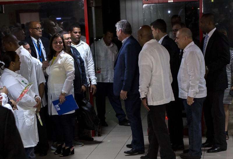 "Cuba's President Miguel Diaz-Canel, center, speaks to Cuban doctors upon their return to Havana, Cuba, Friday, Nov. 23, 2018. The first group of departing Cuban doctors left Brazil Friday after Cuba recalled more than 8,000 doctors rather than meet conditions imposed by Brazilian President-elect Jair Bolsonaro, who said the ""More Doctors"" program could continue only if doctors' pay isn't channeled through the Cuban government and if they could bring their families. (AP Photo/Desmond Boylan)"