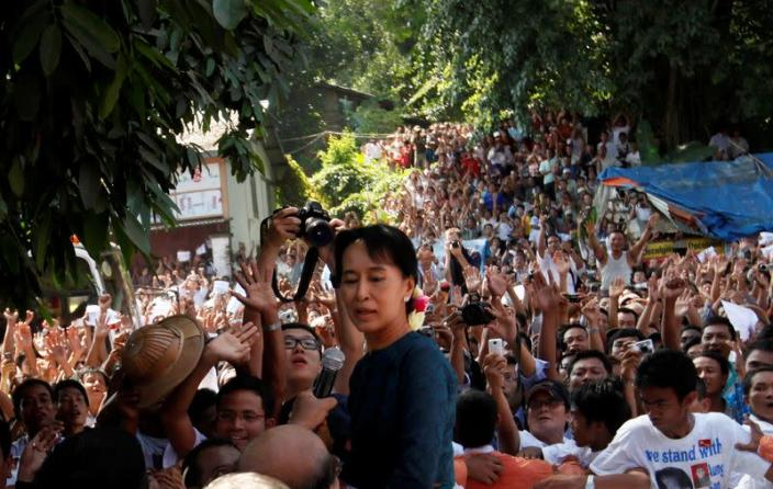 FILE PHOTO: Aung San Suu Kyi stands among supporters gathered to hear her speech outside the headquarters of her National League for Democracy party in Yangon