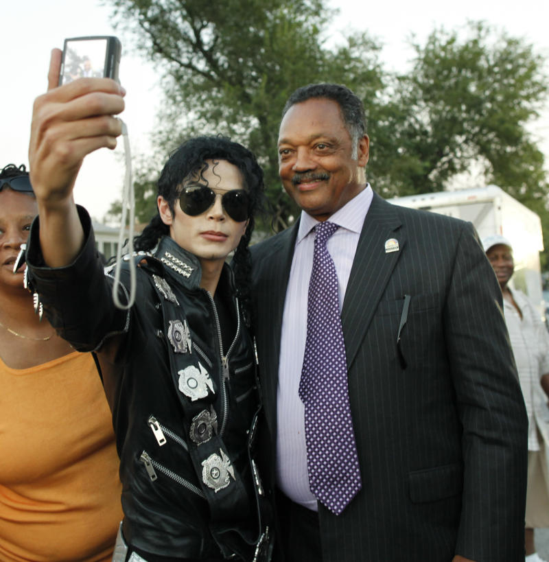 Michael Jackson impersonator Carlo Riley from Denver, left, poses with Rev. Jesse Jackson near Michael Jackson's boyhood home during a celebration marking what would have been Jackson's 54th birthday Wednesday, Aug. 29, 2012, in Gary, Ind. (AP Photo/Sitthixay Ditthavong)