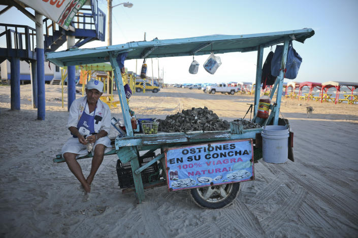 In this Aug. 2, 2019 photo, an oyster vendor snacks on shelled peanuts while he waits for customers in Playa Bagdad near the border city of Matamoros, Mexico. Here, the landscape is not one of walls or border guards; it is simply miles of dunes and Gulf coast beaches, marked only by simple wooden huts or awnings held up by sticks. (AP Photo/Emilio Espejel)