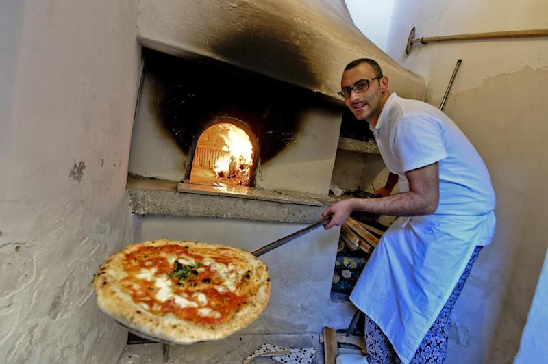 A man shows a pizza cooked in the first stone oven which was used in the 1889 to make the first pizza Margherita in Naples, Italy, Wednesday, Dec. 6, 2017. Italy is waiting a decision by the United Nations Educational, Scientific and Cultural Organisation (UNESCO) to recognize to the Neapolitan pizza in the intangible cultural heritage list. (Ciro Fusco/ANSA Via AP)