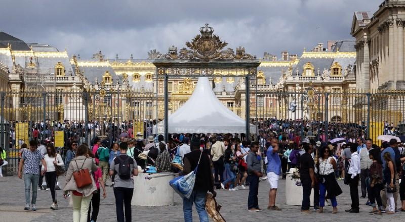 FILE PHOTO: Tourists stand in queue at the entrance to the Chateau de Versailles