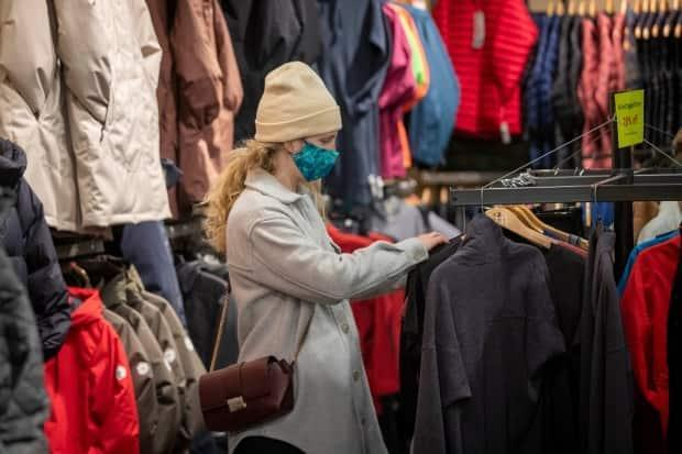 Erin Connolly wears a mask while looking at clothes at Trailhead in Kingston, Ont., Feb. 10, 2021. Unlike the winter shutdown, retail shops can stay open in grey zones. (Lars Hagberg/Canadian Press - image credit)