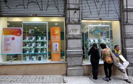 Consumers stand in front of an Oi store, Brazil's largest fixed-line telecoms group, in Sao Paulo